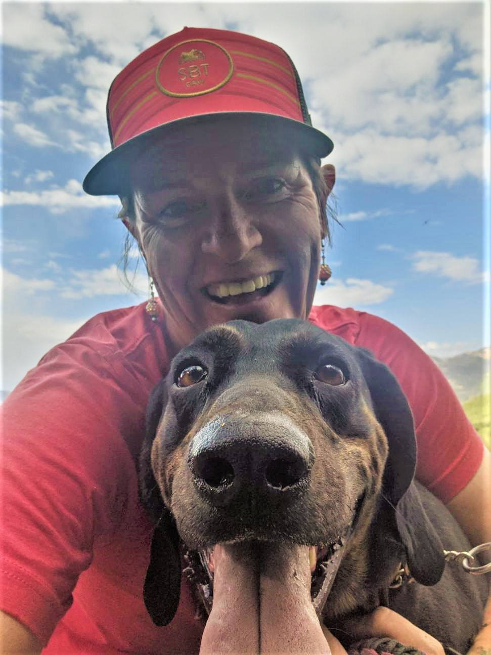 Wild Bunch Desert Guides Laurel Darren smiles widely while hugging her Plott Hound Daisy Mae during a Lake City Hiking Club hike in the breathtaking surroundings of Colorado's San Juan Mountains.