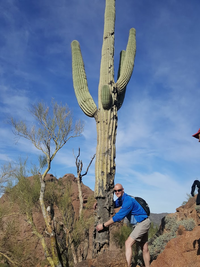 A man hugs a mighty and majestic Saguaro Cactus in the middle of the picturesque Sonoran Desert.