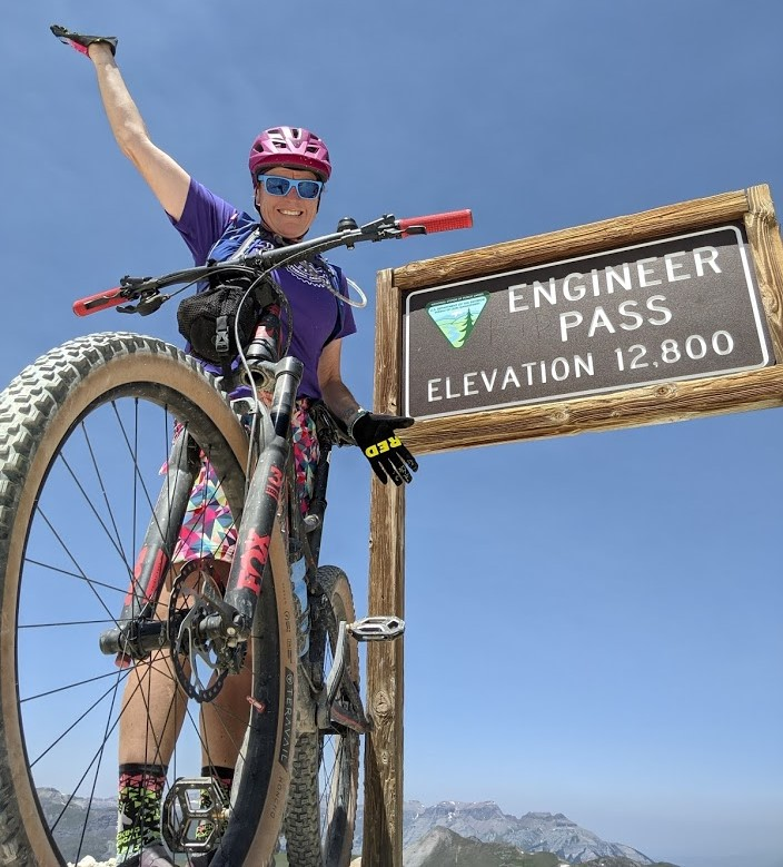 With her right arm raised and trusty mountain bike on her left side, Laurel Darren celebrates reaching the 12,800-foot summit of Engineer Pass in Hinsdale County, Colo. Darren is the owner of Arizona's Wild Bunch Desert Guides, which offers customizable guided Phoenix hiking tours and Scottsdale mountain biking tours.