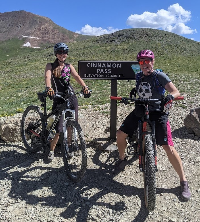 With Colorado's San Juan Mountains providing a beautiful backdrop, Laurel Darren (right) and Lake City local Lydia McNeese pose on their mountain bikes to celebrate reaching Cinnamon Pass. Darren's adventures. part of her summer vacation, also offer daily reminders about her small business, Wild Bunch Desert Guides.