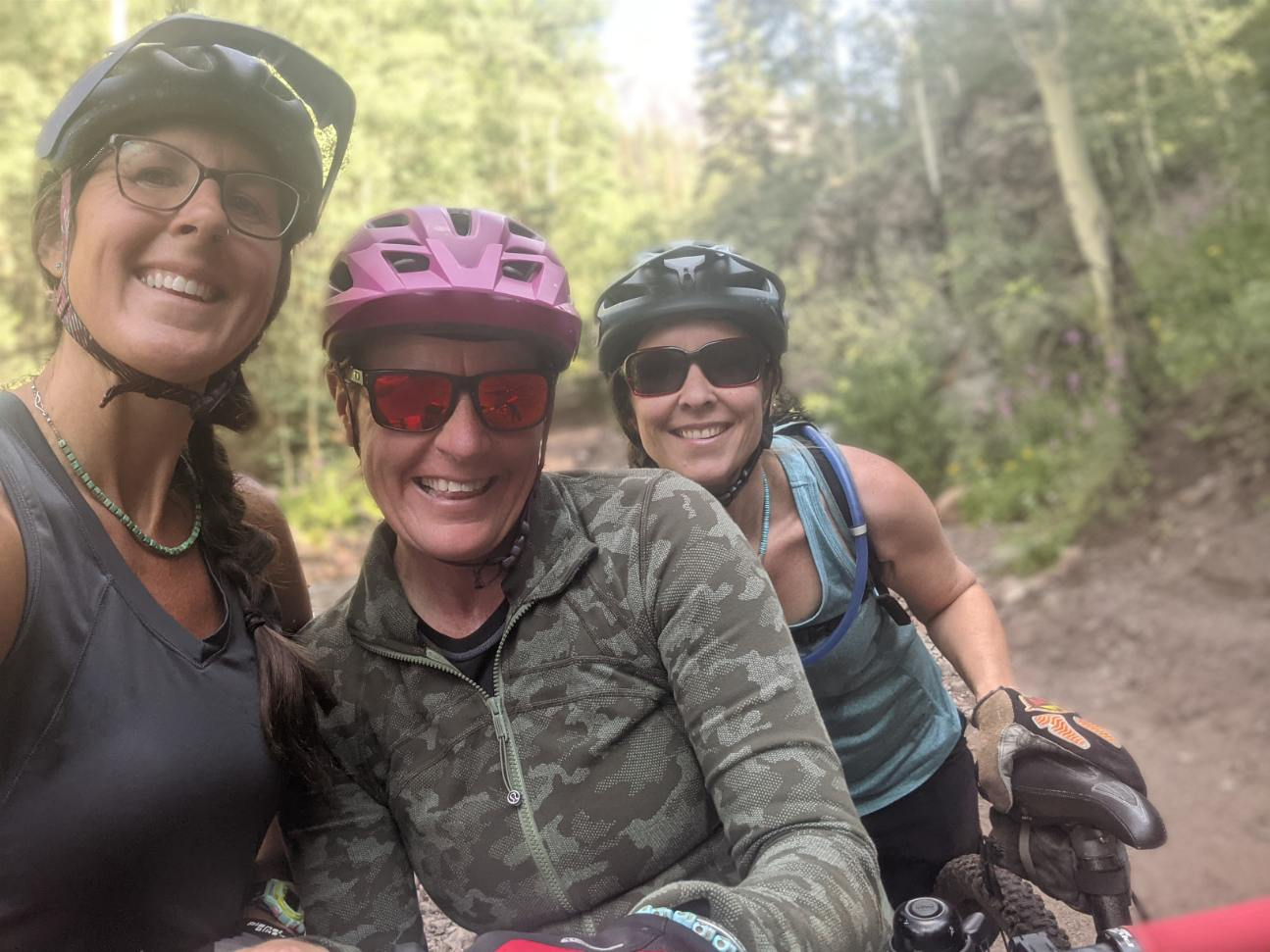 Laurel Darren (center) poses with her Lake City mountain bike pals Amanda Hartman (left) and Lydia McNeese (right) during a training ride this summer. The scenic beauty of Colorado's San Juan Mountains provides an incredible backdrop.