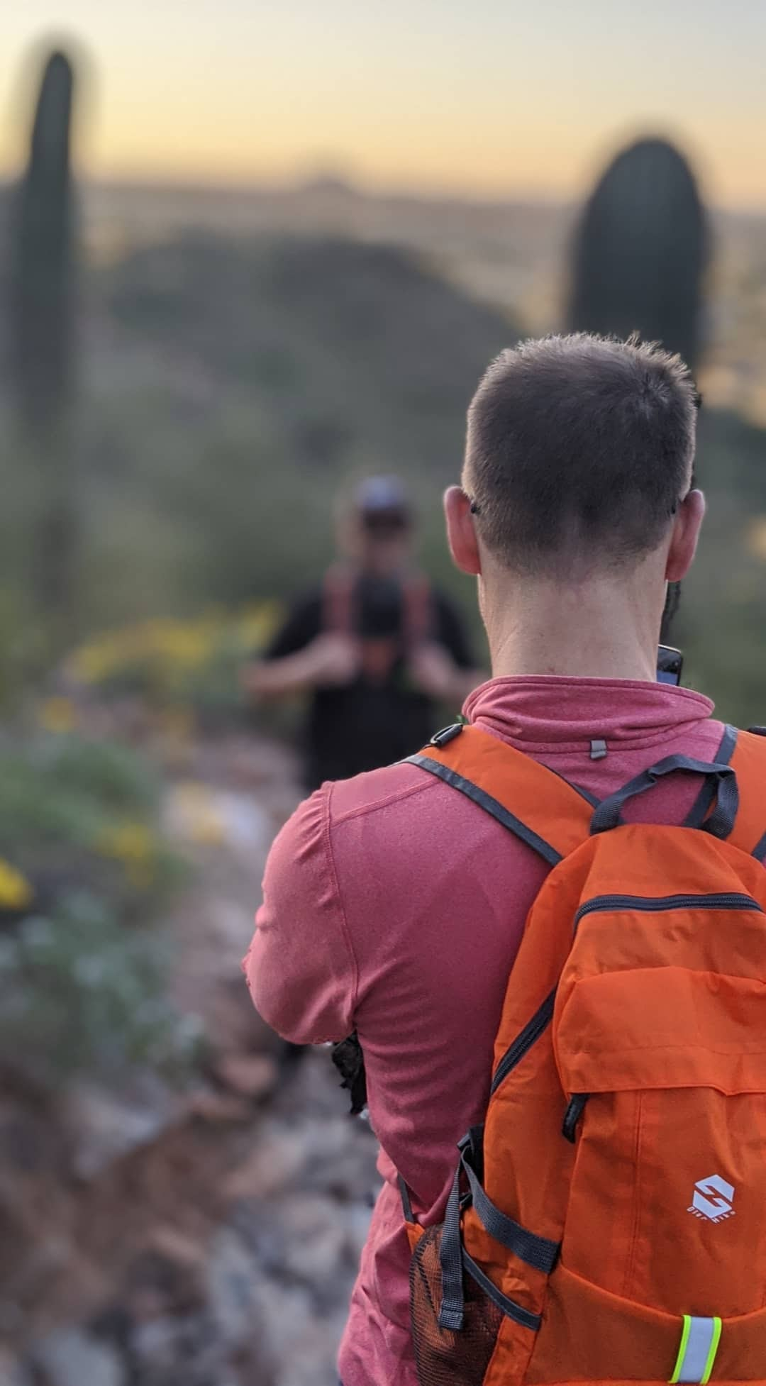 A hiker listens intently to his Wild Bunch guide during a group hike on a particularly majestic Phoenix hiking trail.