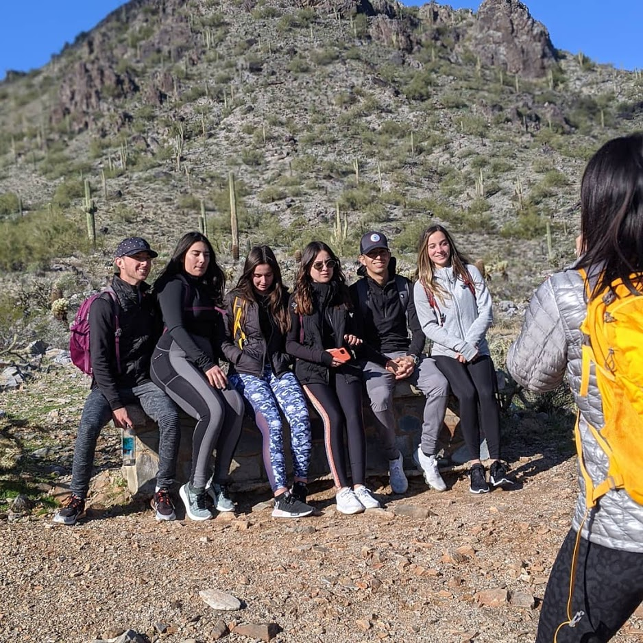 A Wild Bunch group of hikers stops to take a picture with the iconic Southwest scenery during a large group hike in Phoenix.