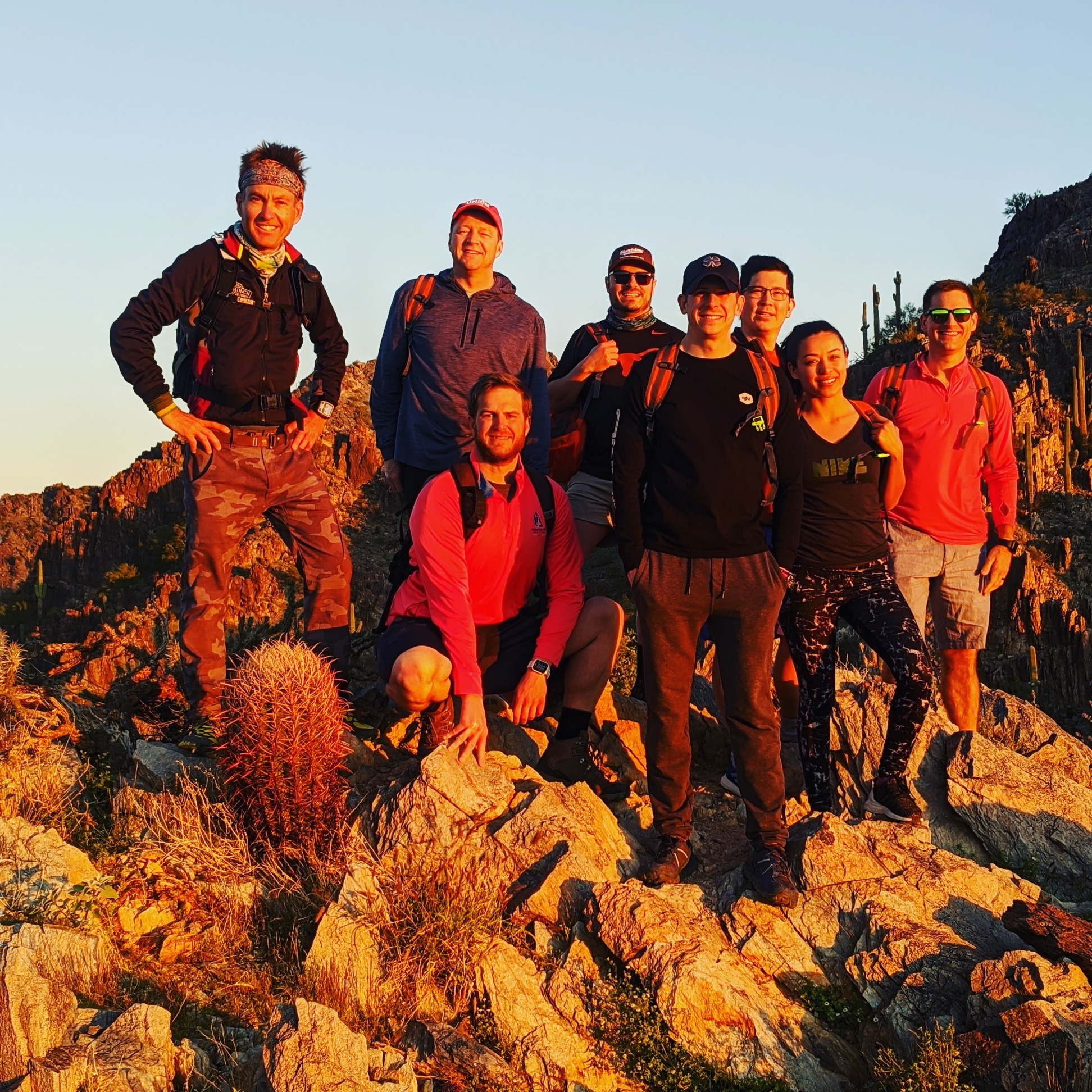 A group of eight hikers happily pose along the rocky terrain of another once-in-a-lifetime guided Phoenix hiking trip with the Wild Bunch Desert Guides.