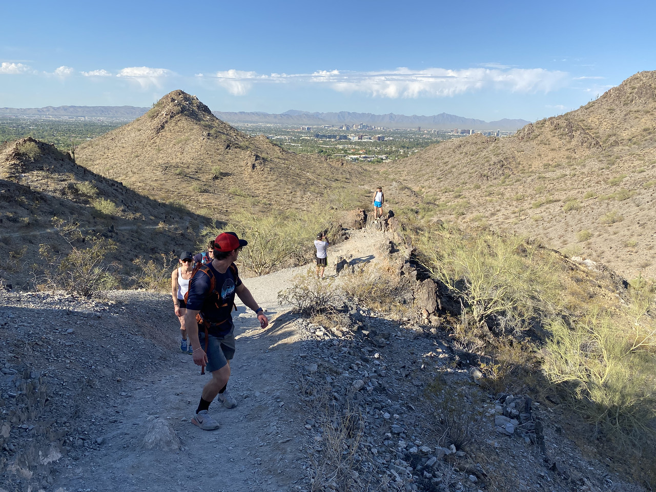 A hiking group makes its way up a scenic hill during a Wild Bunch Desert Guides outing. The leader of the pack (orange hat) peeks over his shoulder to admire the view and spies the last two hikers pausing to take a picture with the sweeping landscape behind them.