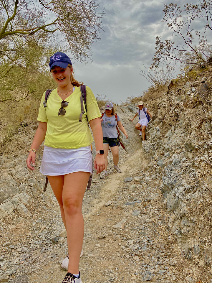 Three women have smiles on their faces as they traverse through a rocky ravine during a Phoenix hiking tour this summer with the Wild Bunch Desert Guides.