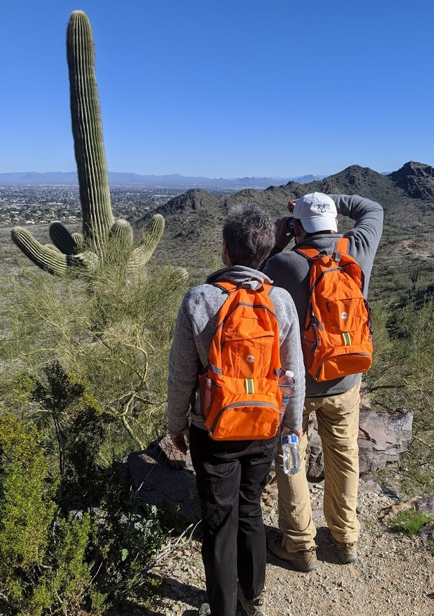 A couple of hikers pause together during a Wild Bunch Desert Guides hiking tour to take a picture of one of Arizona's iconic Saguaro cactuses.