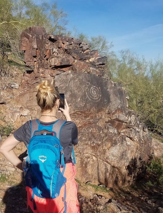 A female hiker pauses in front of a rock formation to take a photo of the Sonoran Desert scenery during a recent guided Phoenix hiking tour with the Wild Bunch Desert Guides.