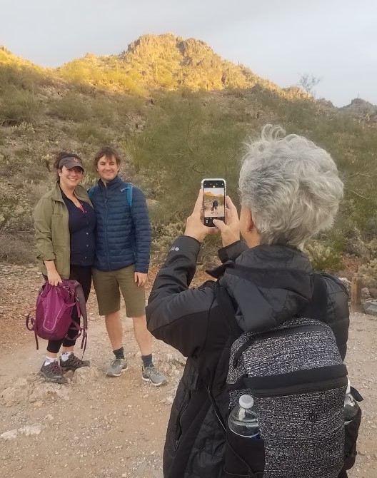 A group of three hikers pause in the early morning cool for a picture in the breathtaking Sonoran Desert scenery after experiencing an amazing Arizona sunrise during one of the Phoenix hiking tours offered by the Wild Bunch.