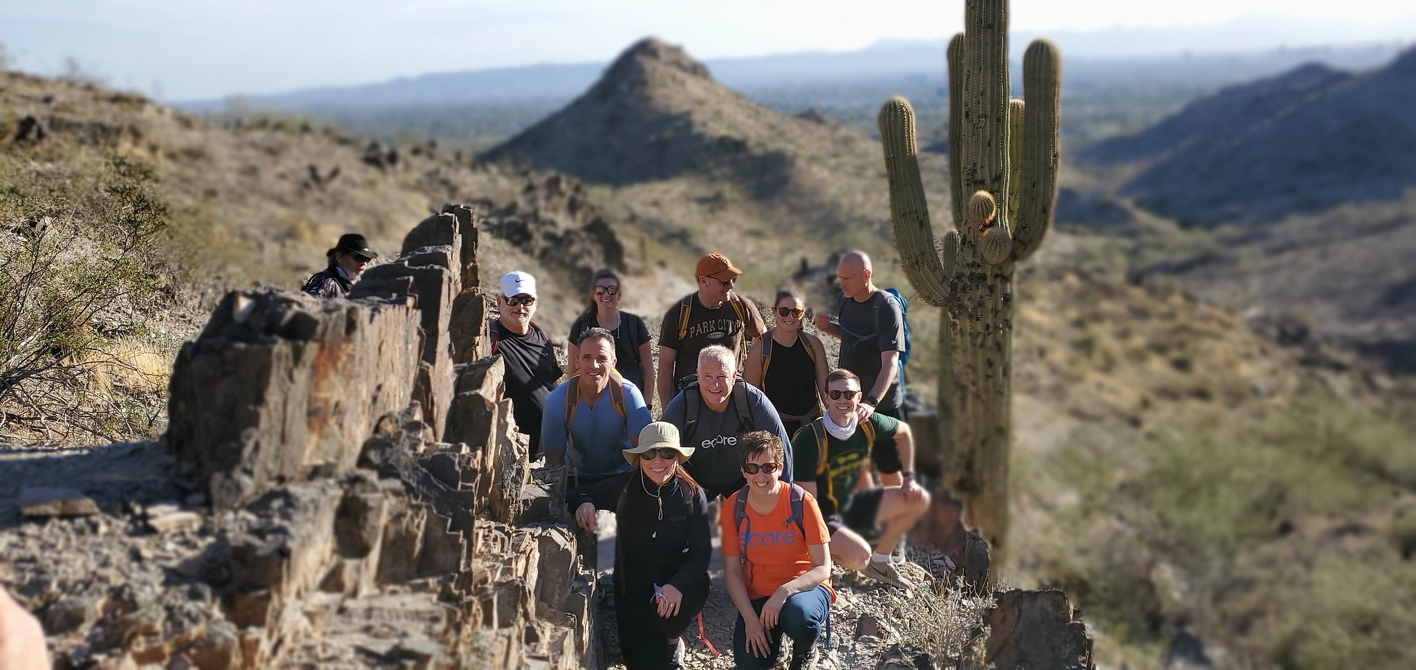 With an incredible desert vista as the backdrop, and a cactus looming over their shoulders, an early-morning summer hiking group pauses for a photo on a particularly picturesque part of their path.