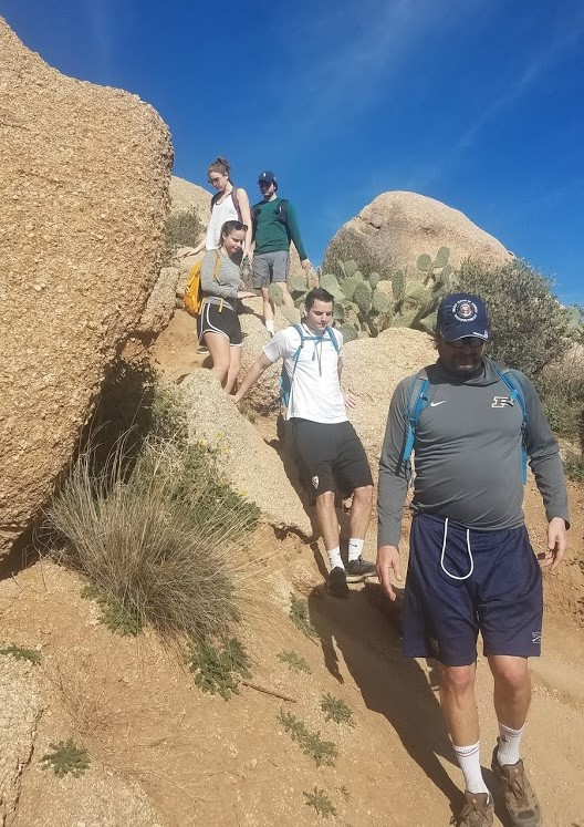 A group of five hikers descends a rock formation during one of the Wild Bunch's recent guided Phoenix hiking tours.