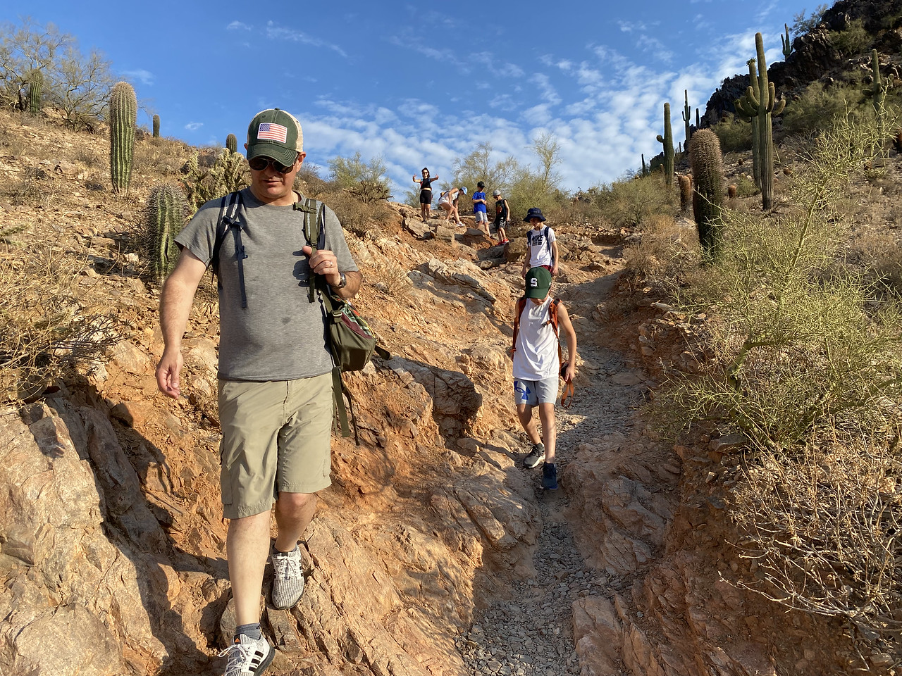 A father is at the front of his family as they stream downhill during one of the Scottsdale hiking tours offered by the Wild Bunch Desert Guides.