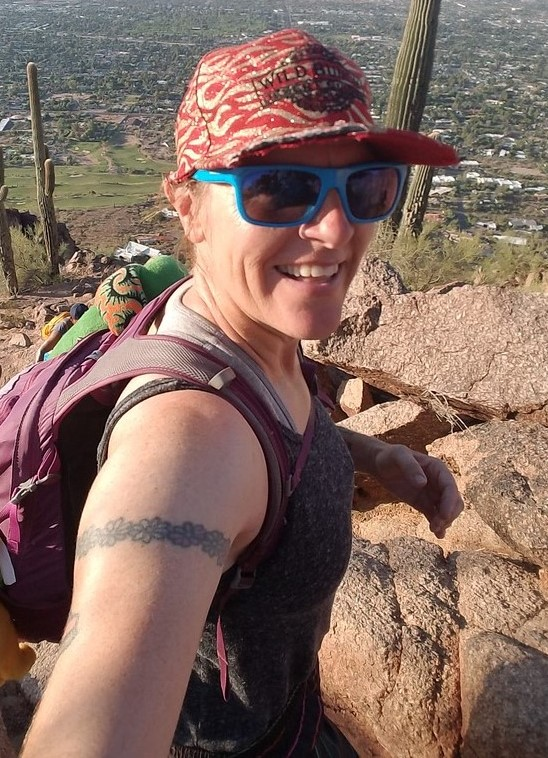 Laurel Darren, owner of Wild Bunch Desert Guides, flashes a wide smile with a breathtaking view as the backdrop during one of our guided Phoenix hiking tours.