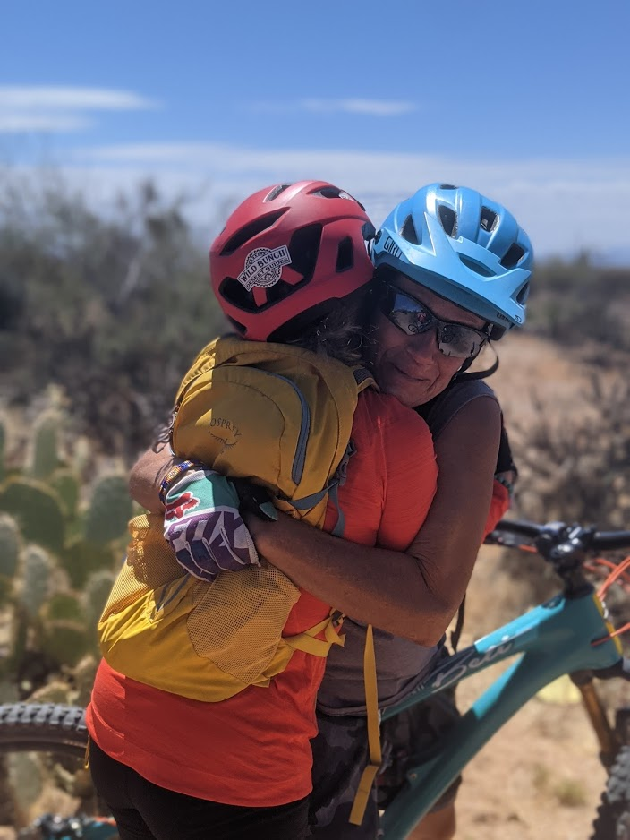 A Wild Bunch guide shares a huge hug with a guest after conquering a challenge on a Scottsdale mountain bike ride in the middle of Arizona's Sonoran Desert.
