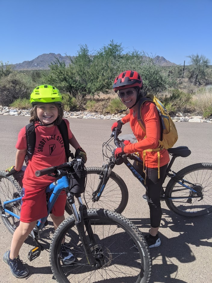 A young girl flashes a big smile after learning to ride a mountain bike with the Wild Bunch Desert Guides. A guide smiles along with her on the trails in Scottsdale, Ariz.