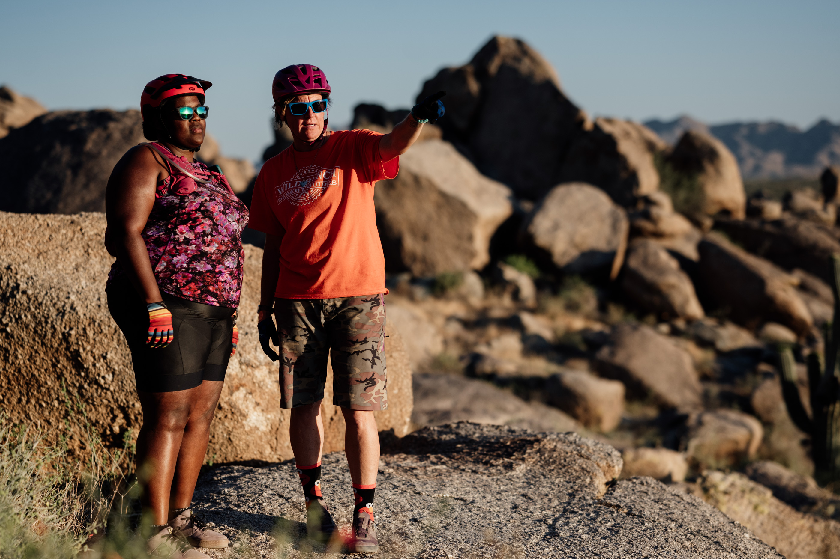Laurel Darren (right) points out some scenery of interest to Mirna Valerio while they stand atop rocky scenery during a mountain bike ride.