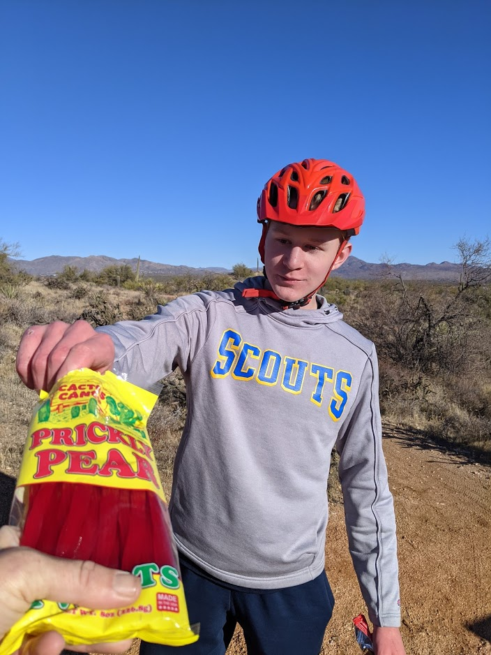 A man accepts the offering of Prickly Pear licorice for a snack break during a Wild Bunch hike.