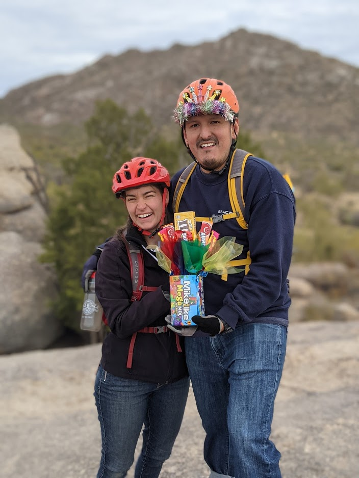 A married couple employed by the cutting-age company Space-X celebrates the husband's birthday with the present of candy on the Scottsdale hiking trails.