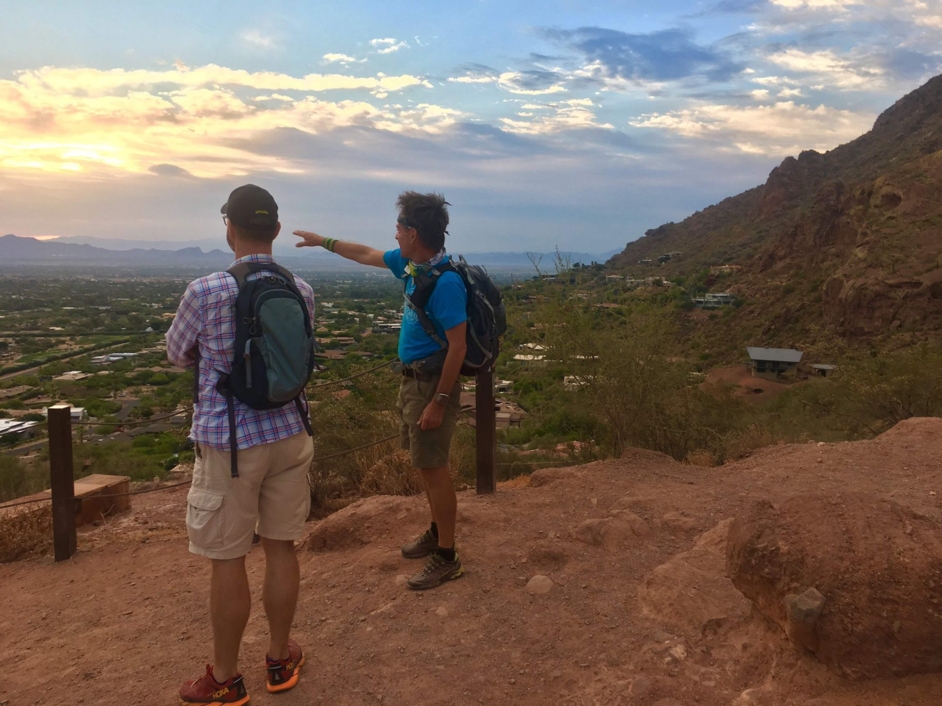 A guide points out several landmarks to a guest while they enjoy the amazing vistas together during a Wild Bunch Desert Guides adventure tour.
