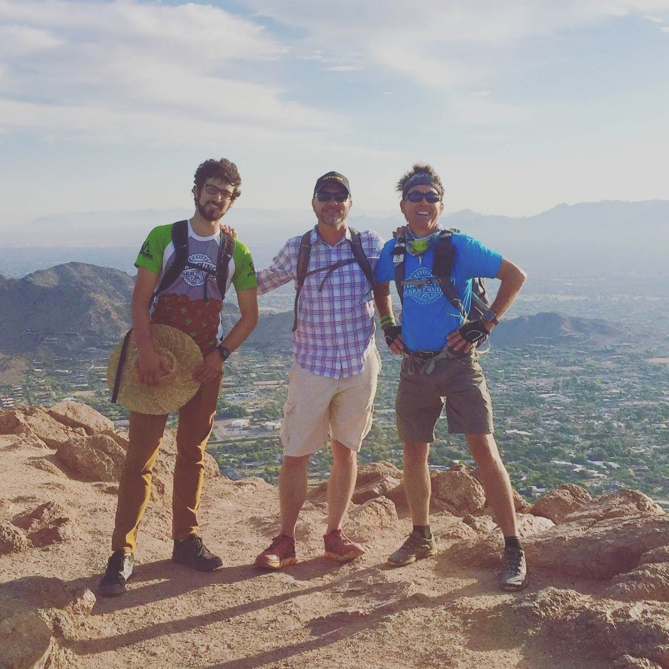 Three WIld Bunch Desert Guides enjoy the views from the summit during a Camelback Mountain hike.